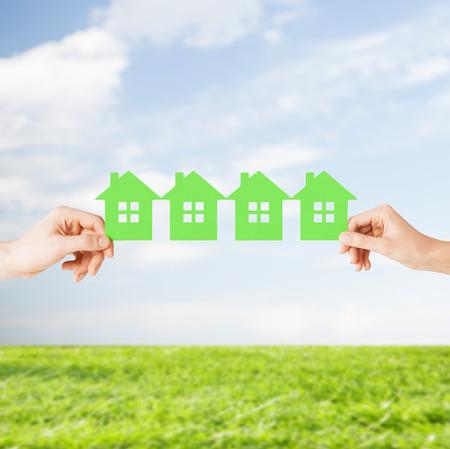 onroerend goed en huis concept - close-up foto van mannelijke en vrouwelijke handen houden veel groen papier huizen Stockfoto