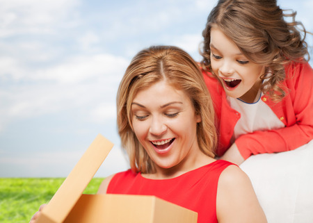 family, child, holiday and party concpt - smiling mother and daughter with gift box photo