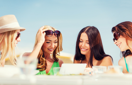 summer holidays, vacation, internet and technology - girls looking at tablet pc in cafe photo