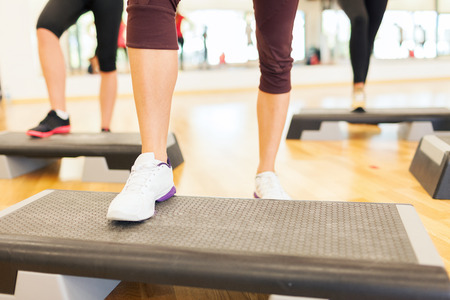 fitness, sport, training, gym and lifestyle concept - close up of women legs steping on step platform in gym photo