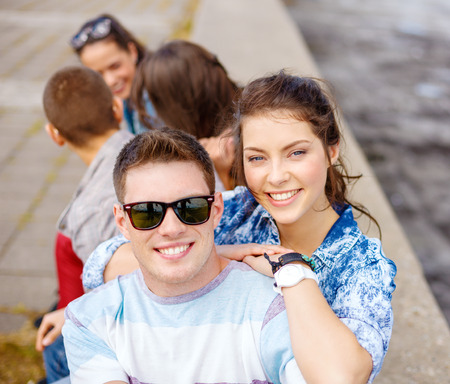summer holidays, relationships and teenage concept - smiling teenagers having fun outside 版權商用圖片