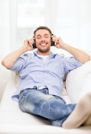 technology, music and happiness concept - smiling young man in headphones at home photo