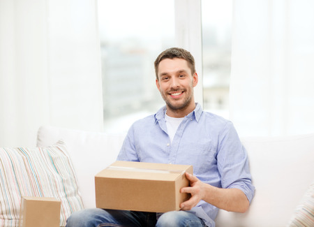 post office: post, home and lifestyle concept - smiling man with cardboard boxes at home