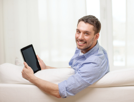 technology, home and lifestyle concept - smiling man working with tablet pc computer at home photo