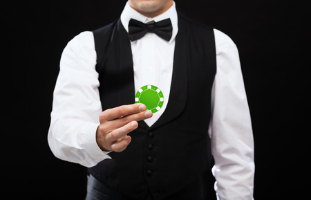casino dealer: magic, performance, circus, casino and show concept - casino dealer holding green poker chip