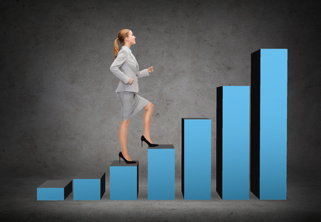 business and education concept - smiling businesswoman stepping on chart bar photo