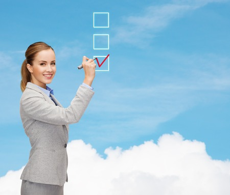office, business and new technology concept - smiling businesswoman writing something in the air with marker Stock Photo