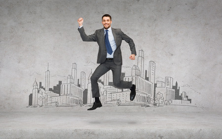 business and education concept - smiling businessman jumping photo