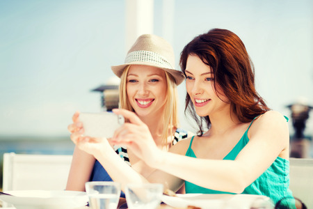 summer holidays and vacation - girls taking photo in cafe on the beach photo