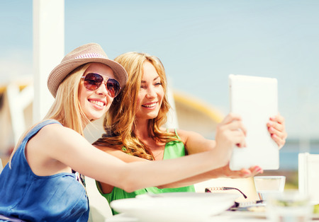 summer holidays, vacation and technology - girls taking photo with tablet pc in cafe on the beach photo
