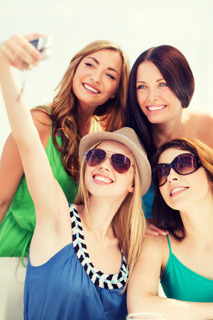 digi: summer holidays and vacation - girls taking photo in cafe on the beach Stock Photo