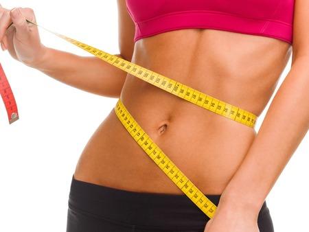 mujer deportista: deporte, fitness y el concepto de dieta - cerca de vientre entrenado con cinta métrica Foto de archivo