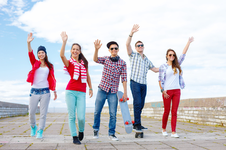 summer holidays and teenage concept - group of smiling teenagers waving hands outside photo