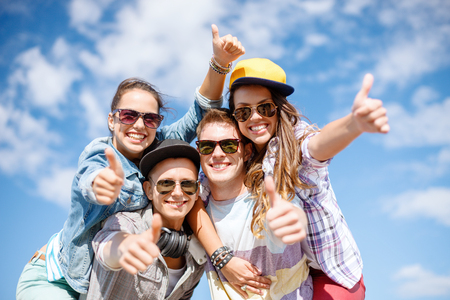 summer holidays and teenage concept - group of smiling teenagers in sunglasses hanging outside and showing thumbs up photo
