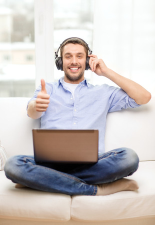 technology, home, music and lifestyle concept - smiling man with laptop and headphones at home showing thumbs up