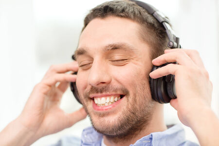 free time: technology, music and happiness concept - smiling young man in headphones at home Stock Photo