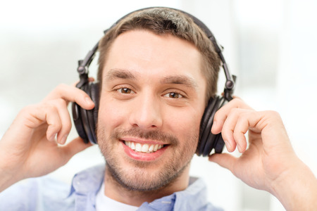 podcast: technology, music and happiness concept - smiling young man in headphones at home Stock Photo