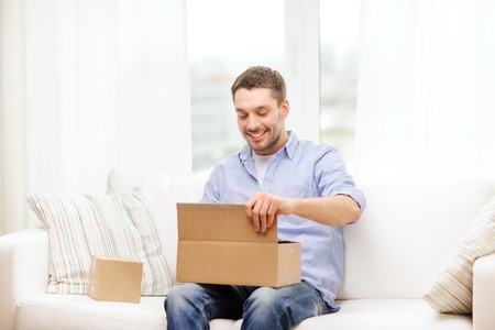 post, home and lifestyle concept - smiling man with cardboard boxes at home photo