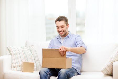 retour: post, huis en lifestyle concept - lachende man met kartonnen dozen thuis