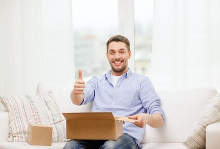 ポスト、家、ライフ スタイル コンセプト - 家庭で段ボール箱を持つ男の笑みを浮かべて親指を現してください。