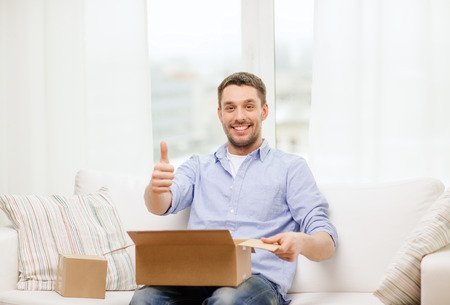 post, home and lifestyle concept - smiling man with cardboard boxes at home showing thumbs up