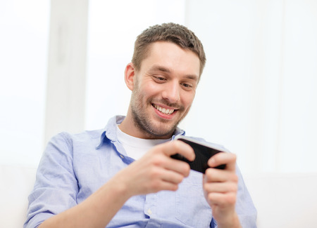 home, technology and internet concept - smiling man with smartphone sitting on couch at home Stock Photo - 27902319