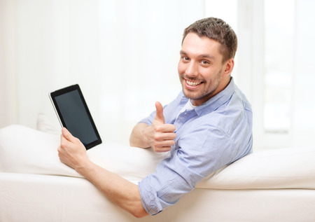 latin man: technology, home and lifestyle concept - smiling man working with tablet pc computer at home showing thumbs up Stock Photo