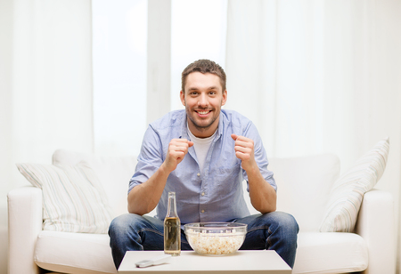 sports, happiness and people concept - smiling man watching sports on tv and supporting team at home photo