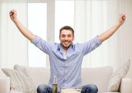 supporting: sports, happiness and people concept - smiling man watching sports on tv and supporting team at home Stock Photo