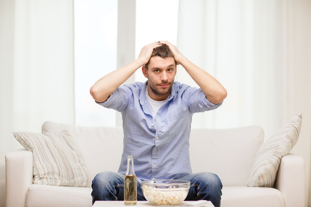 sports, happiness and people concept - sad man watching sports on tv and supporting team at home photo