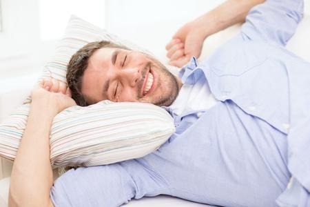 thuis en geluk concept - lachende jonge man liggend op een sofa thuis Stockfoto