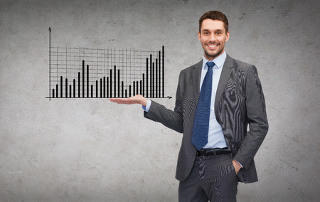 business, office, advertising and people concept - friendly young buisnessman showing growing chart on the palm of his hand photo