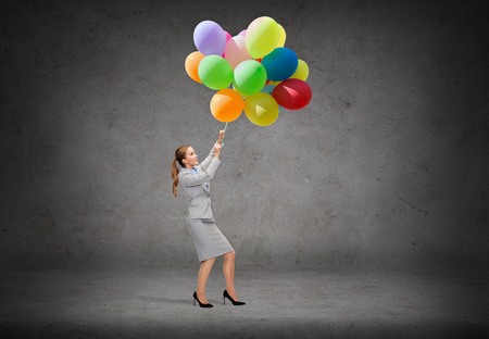 business and education concept - smiling businesswoman pulling down bunch of balloons photo