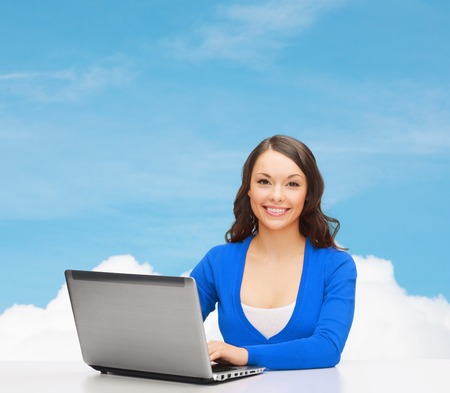 electronics and gadget concept - smiling woman in blue clothes with laptop computer photo