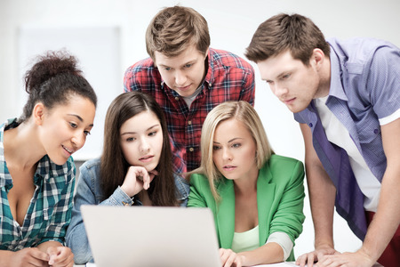 international internet: education and internet concept - group of international students looking at laptop at school