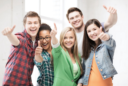 passed: education concept - happy team of students showing thumbs up at school Stock Photo