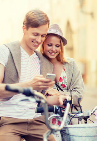 summer holidays, apps and dating concept - couple with bicycles and smartphone in the city photo