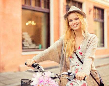 summer holidays, bikes, travel concept - attractive woman with bicycle in the city photo