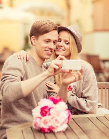 haciendo el amor: vacaciones de verano, las citas y la tecnología de concepto - par la toma de fotografías con el teléfono inteligente en el café en la ciudad