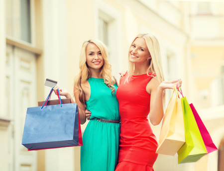 sale and tourism, happy people concept - beautiful women with shopping bags and credit card in the ctiy Stock Photo