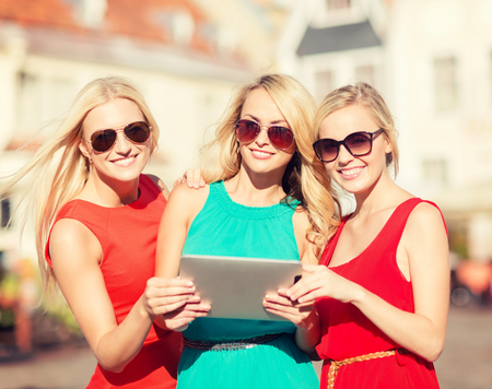 visitors: holidays and tourism concept - beautiful blonde girls toursits looking into tablet pc in the city Stock Photo