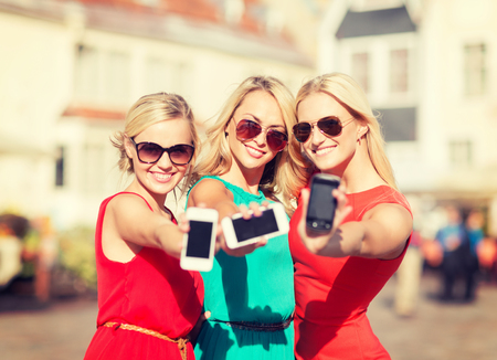 despedida de soltera: vacaciones y el turismo, el concepto moderno de tecnología - hermosas chicas rubias con los teléfonos inteligentes en la ciudad
