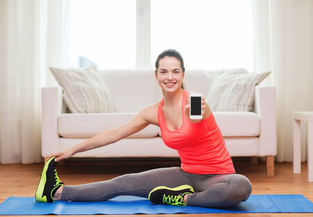 fitness, home, technology and diet concept - smiling teenage girl streching on floor with smartphone at home photo