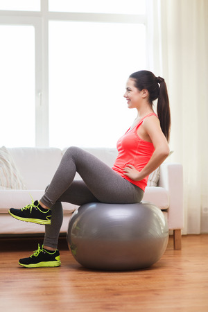 fitness, home and diet concept - smiling girl exercising with fitness ball at home photo