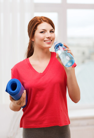 fitness, home and diet concept - smiling teenage girl with bottle of water and yoga mat after exercising at home photo