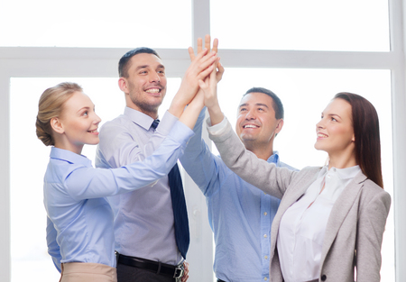 success, business, office and winning concept - happy business team giving high five in office photo