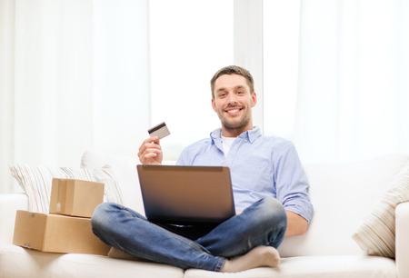 technologie, huis en lifestyle concept - lachende man met de laptop, creditcard en kartonnen dozen thuis Stockfoto