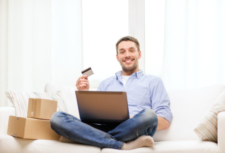 buy online: technology, home and lifestyle concept - smiling man with laptop, credit card and cardboard boxes at home