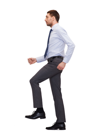 business and education concept - serious businessman stepping on imaginary step photo