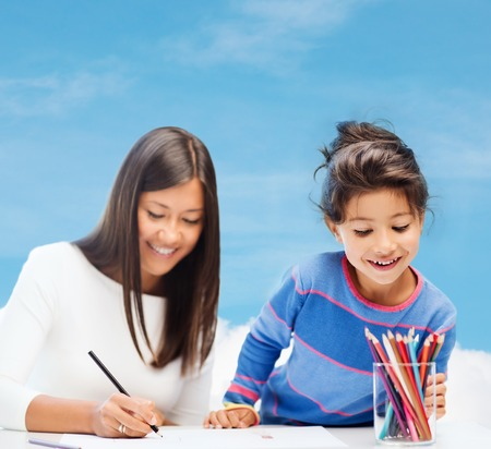 teaching children: family, children and happy people concept - mother and daughter drawing Stock Photo